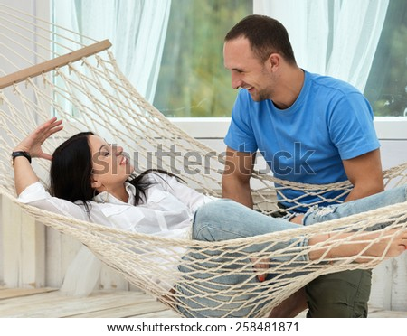 Woman relaxing in hammock smiling and man standing at home - stock photo