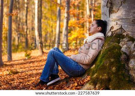 Woman relaxing in nature after a long day at work while autumn season - stock photo