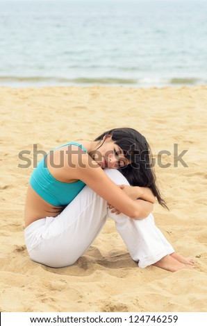 Woman relaxing in peace sitting on sand beach near the sea. Serene woman tranquility on summer morning. Copyspace. - stock photo