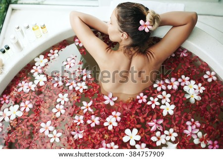Woman relaxing in round outdoor bath with tropical flowers, organic skin care, luxury spa hotel, lifestyle photo, top view - stock photo