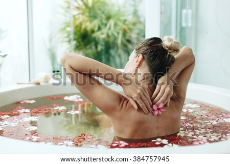 Woman relaxing in round outdoor bath with tropical flowers, organic skin care, luxury spa hotel, lifestyle photo - stock photo