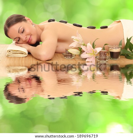 woman relaxing in spa, with reflection on the water - stock photo
