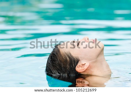 Woman relaxing in swimming-pool - stock photo