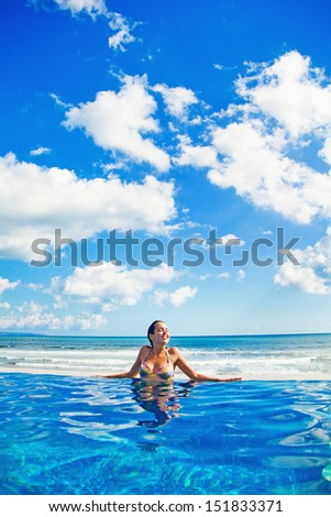 woman relaxing in swimming pool - stock photo