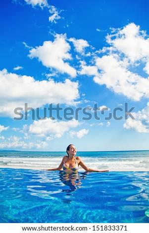woman relaxing in swimming pool - stock photo