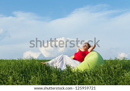 Woman relaxing in the fresh spring grass outdoors enjoying the pale sun - stock photo
