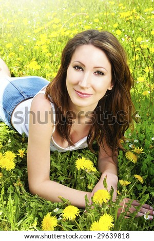 woman relaxing in the grass and flowers - stock photo