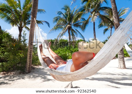 Woman relaxing in the hammock between palm trees - stock photo