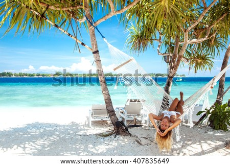 Woman relaxing in the hammock on tropical beach, hot sunny day - stock photo