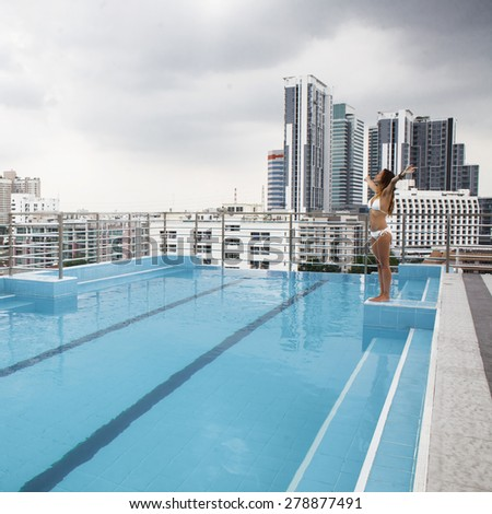 Woman relaxing in the pool on the roof of resort with urban view on skyscraper in Bangkok city - stock photo