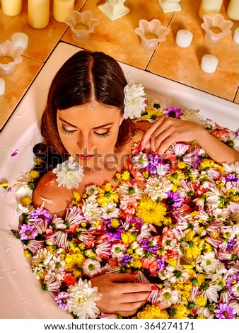 Woman relaxing in warm water with flower.  - stock photo