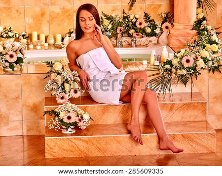Woman relaxing in water spa with a lot of flower. - stock photo