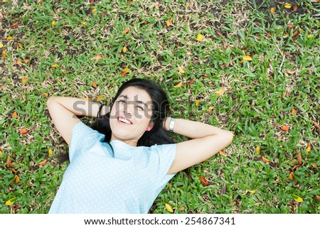 Woman relaxing looking happy and smiling Lying on the grass - stock photo