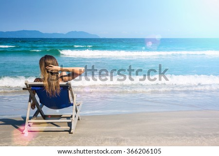 Woman relaxing on a beach chair near beautiful tropical sea, edited with sun flares. Summer vacation concept