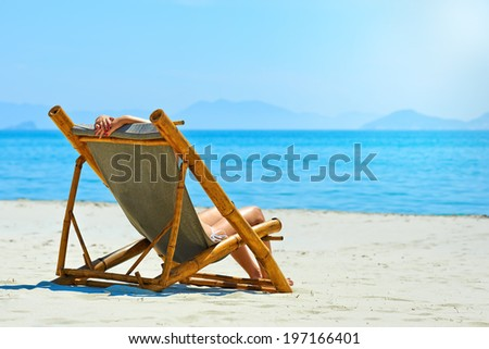 Woman relaxing on a beautiful white beach. - stock photo