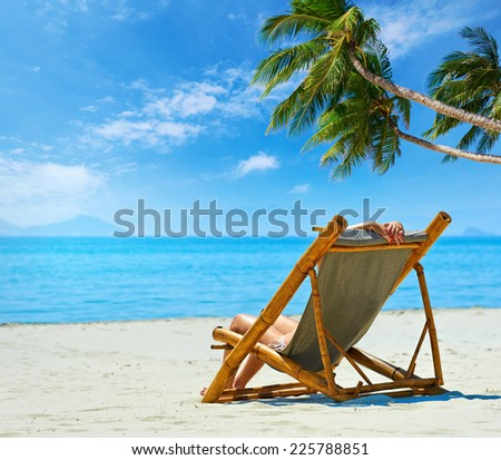 Woman relaxing on a beautiful white beach.