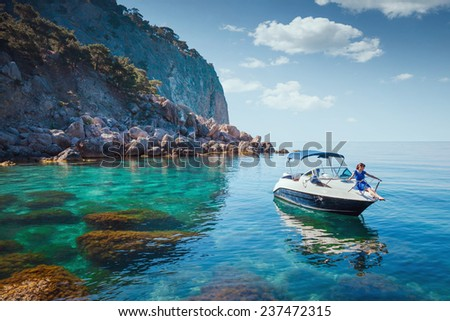 Woman relaxing on a boat in the sea near the rocky shore. Traveling near the island.