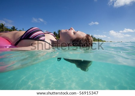 Woman relaxing on a floating tire - stock photo
