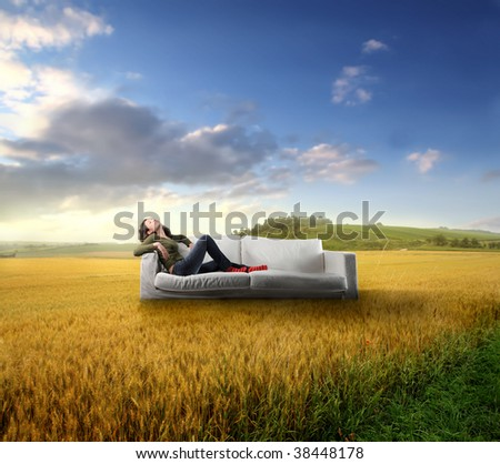 woman relaxing on a sofa in the middle of countryside - stock photo
