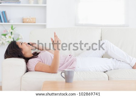 Woman relaxing on a sofa while phoning in a living room - stock photo