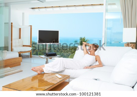 Woman relaxing on a sofa with her bare feet on the coffee table in spacious bright white living-room with glass window overlooking the ocean - stock photo
