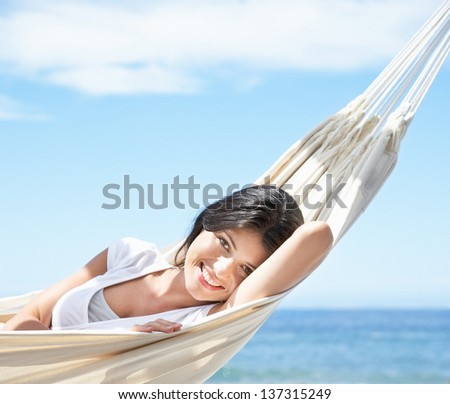 woman relaxing on beach in hammock - stock photo