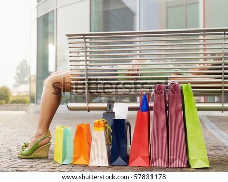 woman relaxing on bench outside shopping center. Horizontal shape, full length - stock photo