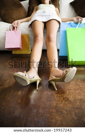 Woman relaxing on couch after long day shopping - stock photo