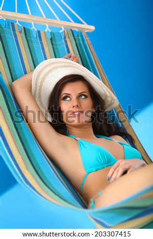 Woman relaxing on hammock with white hat  - stock photo