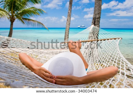 Woman relaxing on hammock with white hat sunbathing on vacation - stock photo