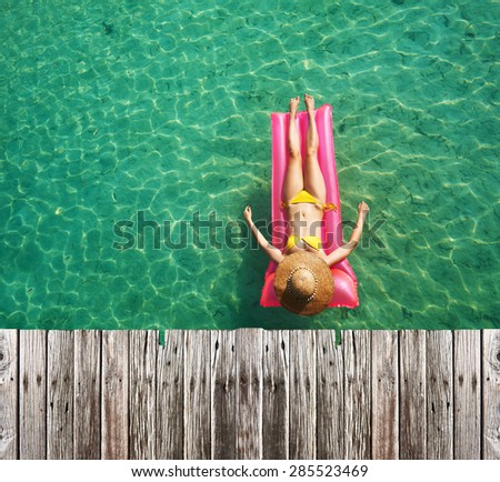 Woman relaxing on inflatable mattress at the beach - stock photo