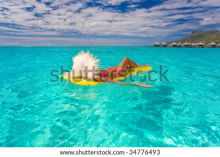 woman relaxing on inflatable raft in turquoise water - stock photo