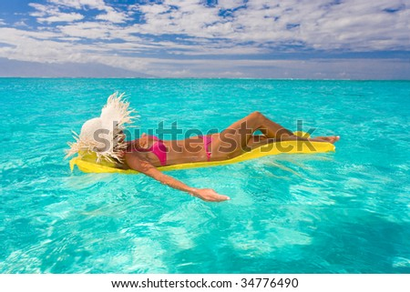 woman relaxing on inflatable raft in turquoise water floating - stock photo