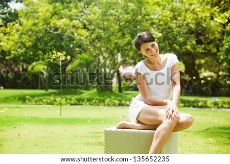 woman relaxing on lounger in the garden - stock photo