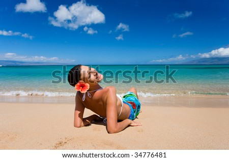 woman relaxing on sandy beach with turquoise waters smiling in maui, hawaii - stock photo