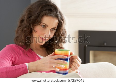 Woman Relaxing On Sofa At Home Drinking Cup Of Coffee - stock photo
