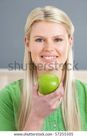Woman Relaxing On Sofa Eating Apple At Home - stock photo