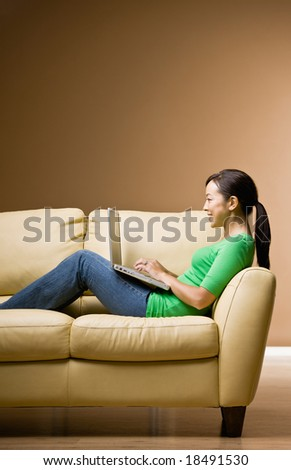 Woman relaxing on sofa in livingroom typing on laptop - stock photo