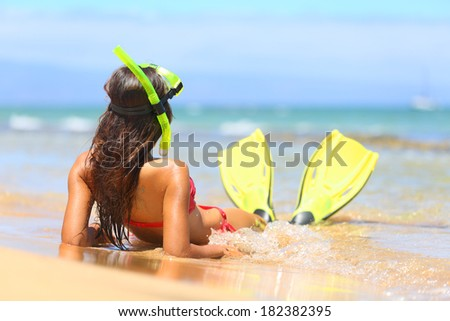 Woman relaxing on summer beach vacation holidays lying in sand with snorkeling mask and fins smiling happy enjoying the sun on sunny summer day on Maui, Hawaii, USA. - stock photo