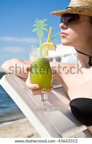 Woman relaxing on summer beach with cocktail - stock photo