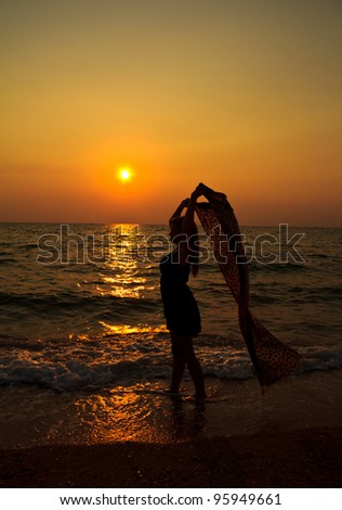 Woman relaxing on the beach at sunset - stock photo