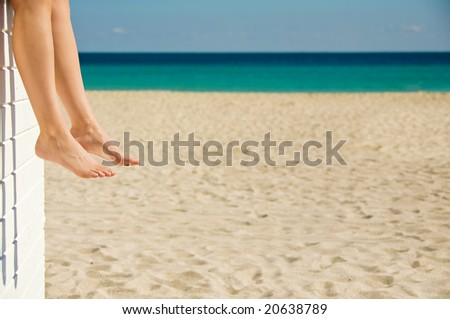 Woman relaxing on the beach on a sunny day - stock photo