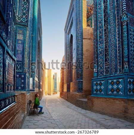 Woman relaxing on the bench and enjoying beauty of the ancient complex of Shah-i-Zinda, Samarkand, Uzbekistan - stock photo