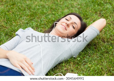Woman relaxing on the grass while listening music - stock photo