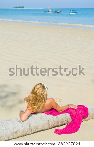 Woman relaxing on the tropical beach by a coconut tree