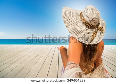 Woman relaxing on the wooden deck by the beach - stock photo