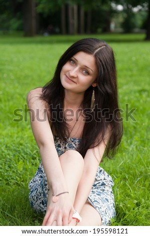 Woman relaxing outdoors looking happy and smiling. Girl sits on grass field in Park