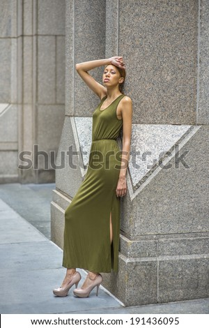 Woman Relaxing Outside. Dressing in a green Maxi Tank Dress, high heels, a hand resting on forehead,   a young black lady is leaning back on columns outside a building, sad, lost in thought.