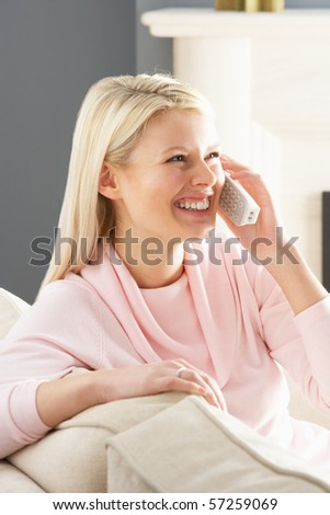 Woman Relaxing Sitting On Sofa At Home Talking On Phone - stock photo