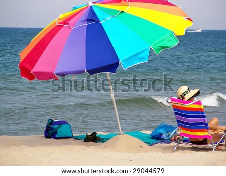 woman relaxing under a bright umbrella - stock photo